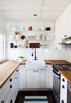 simple kitchen with open shelving, white subway tile and butcher block counters
