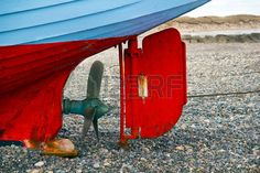 Ship Propeller and rudder A drawn to the beach of old Danish fishing boat Stock Photo