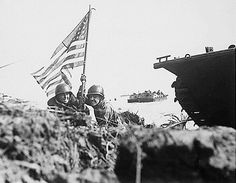 Marines raise the Stars & Stripes in the opening minutes of the U.S. assault on Guam. July 21, 1944.