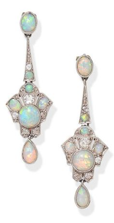 A pair of early 20th century opal and diamond earrings Each pierced geometric cartouche set throughout with opal cabochons and old brilliant and single-cut diamonds, suspending a pear-shaped opal cabochon drop, mounted in platinum, diamonds approx. 0.45ct total, composite, length 4.1cm £ 800 - 1,200 US$ 1,100 - 1,700