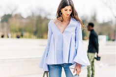 Statement earrings are worn with a structured blouse and denim.