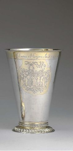 A LATVIAN PARCEL-GILT SILVER BEAKER   MARK OF FRANZ HAGEN, RIGA, CIRCA 1740   Tapering cylindrical, the base gadrooned with bead border, the body engraved with accolé coats-of-arms, the border engraved with an inscription, marked under base, and with accession number  6 5/8 in. (16.8 cm.) high; 11 oz. 10 dwt. (361 gr.)
