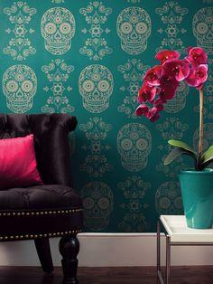 papel de parede com caveiras mexicanas, poltrona preta com almofada rosa, vaso de flor grande na decoração