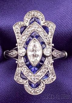 Art Deco Platinum, Sapphire, and Diamond Ring, bezel-set with an old marquise-cut diamond, further set with old mine-cut diamond melee, calibre-cut sapphire highlights, millegrain accents.