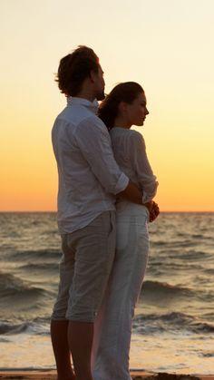 1080x1920 Обои пара, девушка, парень, ветер, море, песок, пляж, прибой, закат, вечер