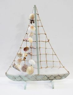 """Sea foam green colored sailboat with rope & seashells for a sail measures 18"""" x 14 1/2""""."""