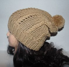 This hat is made in the slouchy style in a lovely tan color. The beanie has braid design alternating through out the hat itself giving it a really nice texture and ends in a big round pom pom!  MADE TO ORDER. Color: Tan Material: 100% very soft acrylic yarn Size: Adult / Teen Machine Wash - Washing and Care instructions sent with every item