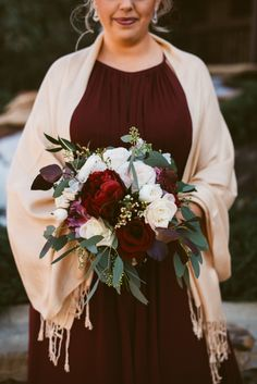 A beautiful, winter bridesmaid bouquet! Love the contrast of the maroon + ivory blooms with the greenery. The perfect wedding colors for your December wedding! Photo taken at THE SPRINGS Event Venue. Follow this pin to our website for more information, or to book your free tour! SPRINGS location: Tulsa, OK Photographer: Blue Elephant Photography #bridesmaidbouquet #bouquet #weddingflowers #winterwedding #winterweddingcolors #winterweddingflowers #weddingcolors #decemberwedding