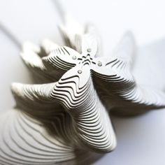 "Orchid Necklace - ""Fifty-one layers of stainless steel are sculpted into a fluid form inspired by the morphology of orchids. This complex design features a simple stacked construction."" $150"
