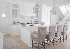 I love the white kitchen and the light colored, wide-plank hardwood floors.