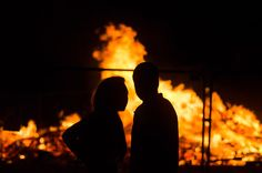 A young couple talk in front of a massive bonfire at West Bay Beach, Dorset. Taken during the annual Torchlight Procession between Bridport and West Bay. pinterest.com/dorsetscouser/