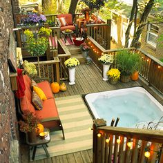 Deck around hottub - deck is flush, with a finishing board, outdoor sofa and carpet make it a cozy room. Hooks above the sofa provide space to hang towels and robes. Planters provide privacy and beautiy. rope lights tie it all together an provide illumination day or night.