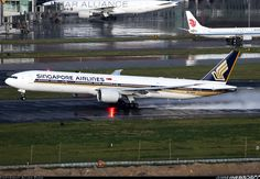 A Singapore Airlines 777-300ER rotating on a wet day at Beijing Allen Zhao
