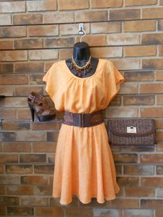 We love this eye catching orange dress! It looks great with a belt and sexy heels!