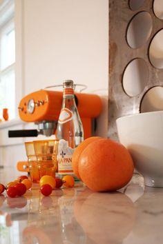 An orange espresso machine, orange vintage glassware and oranges in the home of Alissa Pulcrano