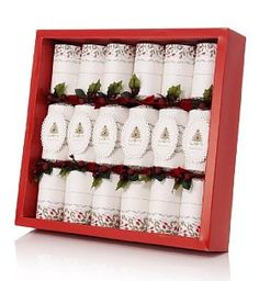 6 Red & White Tree Connoisseur Christmas Crackers. Add a seasonal finishing touch to your Christmas dinner table with this pack of 6 elegant Christmas crackers in white with pretty Christmas tree plaques, leaves, berries and red ribbon bows. These crackers contain grown-up luxury gifts which are more suitable for adults, making them perfect for special dinner parties and festive occasions. You must be 16 or over to purchase this product. Approx. size: H360 x W60mm (each cracker) 6 crackers…