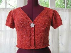 Use this free knitting pattern to make a woman's puffed sleeve cardigan featuring a fitted silhouette, v-neck, cropped length, gathered cap sleeves, knit-in borders and an eye-catching rhinestone single button closure. Knitting Patterns Free, Free Knitting, Free Pattern, Learn How To Knit, How To Start Knitting, Short Sleeve Cardigan, Cardigan Pattern, Knitwear, Tunic Tops