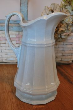 Beautiful Tall Ironstone pitcher, antique, with elegant lines and graceful detailing on the handle. Small chip on top. 11 inches tall. Very faint