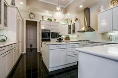 Sleek, white kitchen. And great place for a chandelier!