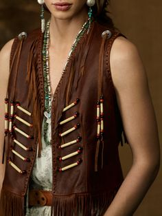 """Hairpipe Leather Vest Price: $498.00   Sale Price: $379.99 Style #18358776   This supple leather vest exudes Southwestern-inspired style with fringe accents and festive beaded trim.      V-neckline. Beaded trim along the front.     Sleeveless silhouette with buttoned tassel drops.     Single row of beaded fringe across the back.     Fringed hem.     22"""" length. 100% leather. Dry clean. Imported"""