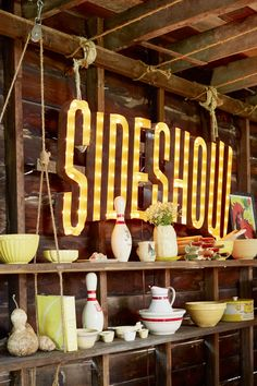 """Along the barn's kitchen wall, Cooper repurposed boards looped with jute rope into a rustic shelving unit. His collection of yellowware bowls, interspersed with quirky """"bits and bobs"""" (including a sign that gives a nod to his latest album), adds a pop of color."""