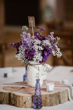 White mason jar centrepiece with purple and white flowers and a burlap table number. Lavender & Plum Wedding Ideas