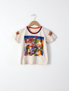 A vintage 1970s Shogun Geta t-shirt. The little white t-shirt features an orange and blue ringer collar. It has anime imagery on the front with the