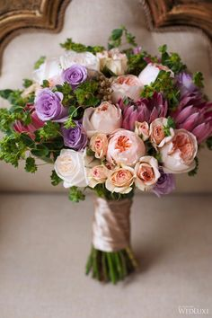 Touches of petal pink and peach enhance this purple wedding bouquet