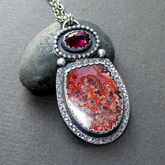 This item is now reserved - thank you!        The colors in this piece are just fabulous! In this colorful necklace Ive paired a 21x27.5 mm Laguna Lace Agate with a beautiful 8x10mm Rhodolite Garnet. Both stones are set using 20 gauge sterling silver as the back plate. Ive added some hand texturing around the agate and a beaded frame around the Garnet. Total height of piece from top of hanging loop to bottom is about 1 7/8. Pendant hangs from a sterling silver cable style chain which Ive…