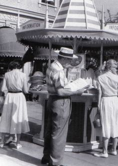 An incognito Walt Disney pursues a park guide book, date unknown (likely 50's).