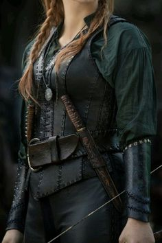 Inspiration for Mira's look. She had a black leather jerkin over a dark, sage green shirt. The flowing sleeves were bound at her forearms by black braces, and on her belt hung twin daggers. ---// her comfort Armor Cosplay, Medieval Clothing, Gypsy Clothing, Medieval Fantasy, Medieval Gown, Fantasy Armor, Dark Fantasy, Character Outfits, Warrior Princess