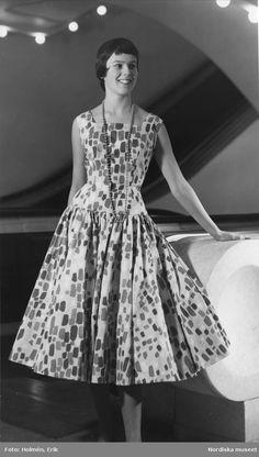 Bild från Nordiska Kompaniets Viola Gråsten - utställning 1955. Modell klädd i mönstrad klänning och långt pärlhalsband står framför rulltrappor.