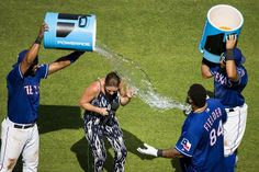 Emily Jones tries to duck away from a bucket of water tossed her way by Elvis Andrus