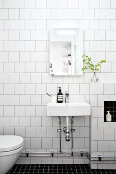 Schicht und doch so liebevoll: ein Badezimmer im strahlendem Weiß mit Subway-Tiles und einem Handwaschbecken #bathroom #bathdesign #tiles #washstand #basin #sink #waschbecken #mirror #badezimmer #badezimmerideen #calmwaters #flower #bad #interior