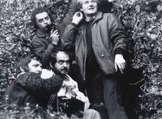 Director Stanley Kubrick on the Hedge Maze set of The Shining, flanked by Director of Photography John Alcott, Focus Assistant Douglas Milsome, and an unidentified crew member.