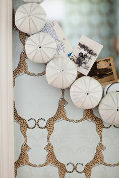 I made this mirror myself by gluing painted white urchins around the edge. I like to stick old pictures and notes on the mirror – they make me smile every time I pass by. Wallpaper is Thibaut.