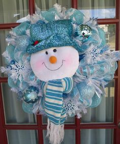 Merry Christmas Holiday Snowman Deco Mesh Wreath is made with deluxe Baby Blue & White,  deco mesh. The 24 inch 8 inch deep wreath is trimmed with cute little snowflakes,Beautiful Christmas Bulbs,