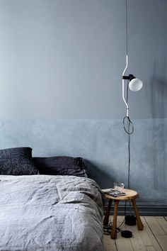 A serene and peaceful gray color palette, cozy textures and FLOS Parentesi lighting all come together seamlessly in this minimalist modern bedroom.
