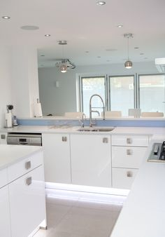 White Gloss Nolte Kitchen with bright blue glass splashbacks and ambient lighting German Kitchen, Kitchen Manufacturers, White Gloss Kitchen, Glass Splashback, Kitchen, Kitchen Range, Ambient Lighting, Blue Glass, Bespoke Kitchens