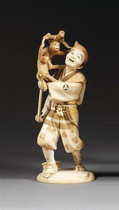 OKIMONO en ivoire rehaussé d'encre, représentant un sarumawashi accompagné de ses trois singes grimpés sur une perche surmontée d'un arceau. Signé dans un cachet doré. (Gerçures). Japon, période Meiji (1868-1912). AN IVORY FIGURE, SIGNED, JAPAN, MEIJI PERIOD. HAUT. 27,5cm (10 13/16 IN.)