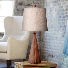 Use the natural charm and elegant of this contemporary table lamp, with a faux wood finish, to bolster your decor with added detail.