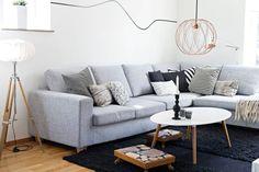 ENKLE GREP I STUA: Sofaen er fra mio.se. Lignende får du hos BoConcept. Sofabordet er fra en nedlagt butikk. Taklampen i kobber har Sofie funnet på et loppemarked. De to små puffene lagde Sofies oldefar en gang i tiden, men Sofie har trukket dem om i et moderne stoff fra Ikea. Skrivebordslampen som har tilhørt Sofies far, har fått litt kobberfarge på innsiden av skjermen. Det gir et varmt og fint lys. FOTO: Emma Olai