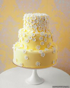 Daisy Wedding Cake Sugar-paste daisies drift down a bright yellow fondant-covered cake by Gail Watson of New York City. Accessories www.allofyou.etsy.com