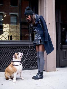 Mujer con medias y abrigo hablando con su perro bulldog