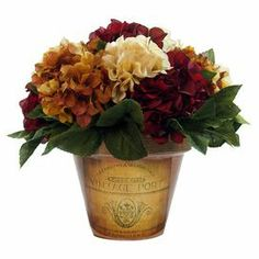 """Silk hydrangea arrangement in a clay planter with French typography.  Product: Faux floral arrangementConstruction Material: Clay, plastic, silicone and silkColor: Orange and burgundyFeatures: Includes faux hydrangeasDimensions: 14"""" H x 13"""" DiameterNote: For indoor use only"""