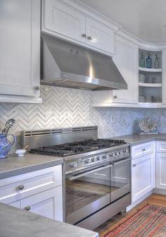 gorgeous white kitchen, wood floors, gray counters, herringbone/chevron tile backsplash.