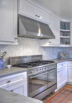 gorgeous white kitchen, wood floors, gray counters, herringbone/chevron tile backsplash.