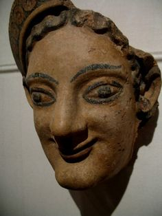 """This Etruscan piece dates from the 6th century BCE. It is described as Terracotta with black and red pigment. The museum has titled it:  """"Female head antefix"""""""