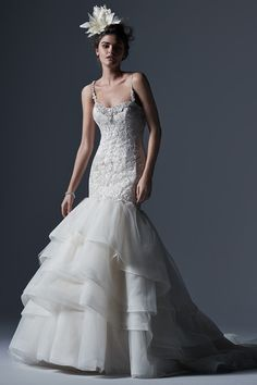 <strong class='info-row'>Maggie Sottero Designs</strong> <div class='info-row description'>Style Hamilton   Understated drama is found in this fit and flare wedding dress with fitted lace bodice and voluminous tiers of tulle and Chic organza layered throughout the skirt. Glamorous Swarovski crystals adorn the sweetheart neckline. Finished with zipper closure. Glittering Swarovski crystal strap and back detail offered separately.</div> <div class='row info-row text-center'> <div…