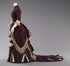 c. 1800 ... Afternoon dress ... American ... silk & abalone ... The nuances and contrasts between the plain faille against the subtly figured aubergine and cream silk are particularly effective on this gown. The train in particular shows interesting contrasts. Using that kind of detail on the train shows the level of awareness and scrutiny under which the design of the dress would be under. ... at The Metropolitan Museum of Art ... photo 2